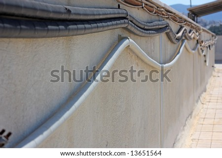 Protected electrical cables along a roof wall (focus on the first curve of the lower cable)