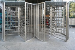 Protected entrance gate  secured turnstiles outdoors. Steel revolving turnstiles at the entrance of production or metro station. Closeup of steel revolving security turnstile on the street