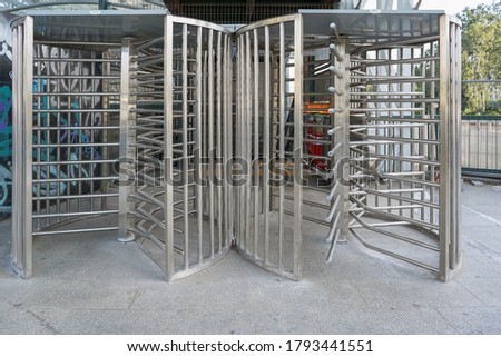 Protected entrance gate  secured turnstiles outdoors. Steel revolving turnstiles at the entrance of production or metro station. Closeup of steel revolving security turnstile on the street Foto stock ©