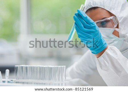 Protected science student holding a test tube in a laboratory