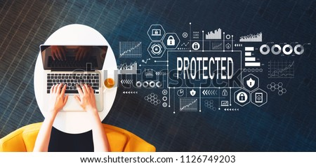Protected with person using a laptop on a white table #1126749203