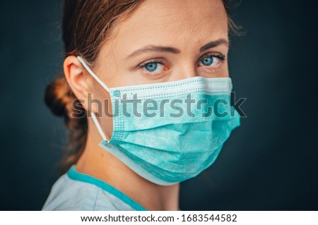 Protection against contagious disease, coronavirus. Female doctor wearing hygienic face surgical medical mask to prevent infection, respiratory illness as flu, 2019-nCoV. Studio photo black background