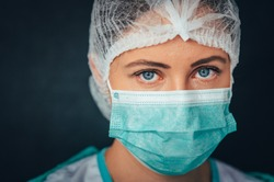 Protection against contagious disease, coronavirus. Portrait Photo. Female medical worker wearing protective face mask, head cover and suit inside hospital ward