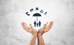 Protection against germs, viruses. Medical and pharmaceutical concept, hands hold the family icon covered with umbrella protecting against bacteria, viruses. Disease prevention.