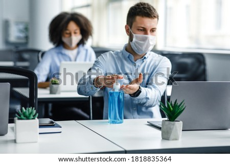Protection at coronavirus pandemic in office. Young man in protective mask works at laptop and disinfects his hands with antiseptic