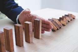 Protection finance from domino effect concept. Hands stop domino effect before destroy stack of money.
