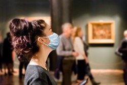 Protection from the virus. A tourist visits the sights of the Museum in a medical mask. People and pictures in the background. The concept of a viral pandemic and maintaining distance