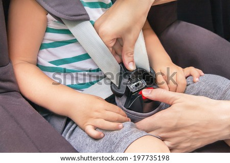 Protection in the car. Hands of caucasian woman is fastening security belt to child, who is sitting in safety car seat (chair). Toddler has a trip in summer day. Vehicle and transportation concept.