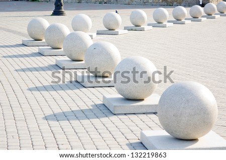 Protection in the form of decorative stone spheres on sidewalk