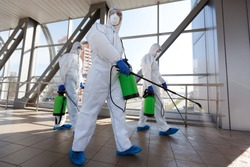 Protection of coronavirus biohazard. Men in respirators and protective suits cleaning public places with chemicals, copy space