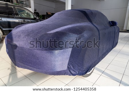 Protective cover awning for cars, blue, made from special material, bespoke at the auto repair shop, covering an expensive sports car, prepared for winter storage and exploitation. #1254405358
