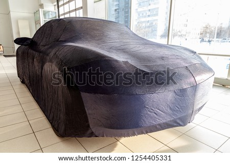 Protective cover awning for cars, blue, made of special fabric, custom-made at the auto repair shop, covering an expensive sports car, prepared for winter storage. #1254405331