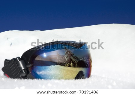 protective eyewear for winter sports and recreation on the background of snowy mountains and blue sky