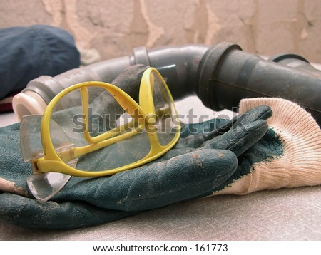 Protective glasses and working gloves and a pipe