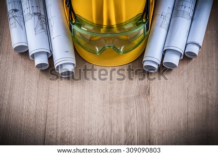 Protective glasses construction plans and building helmet on wooden surface.