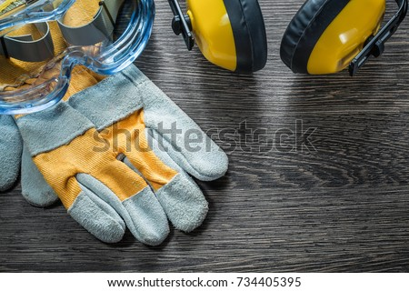 Protective gloves safety glasses earmuffs on wooden board. #734405395