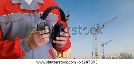 protective headphone at man hands on building background