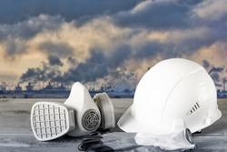 Protective helmet of white color, respirator and work gloves against the background of smoking chimneys of a chemical plant. Workplace safety concept.