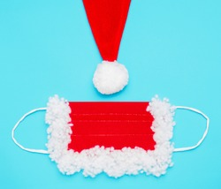 protective mask and part of a hat with a pompom for Santa Claus, red and white, on a blue background