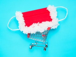 protective mask of santa claus (red and white) in a trolley from the store on a blue background, flat lay