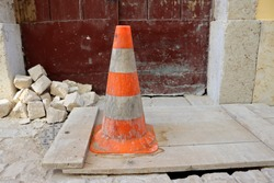 Protective orange cone. The hole near the entrance to the house is covered with a wooden board and an orange traffic cone. Dangerous hole in the road