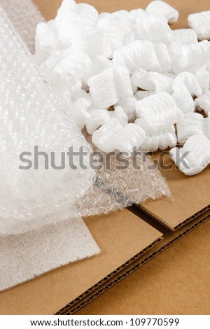 Protective packaging materials atop brown corrugate boxes show an assortment of shipping supplies