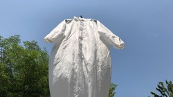 Protective PPE suit hanging outdoor after the used and washing,natural glare light,the ppe suit can to repeated use 2-3 times,after use every day should wash and dry in the sun,prevented covid-19.