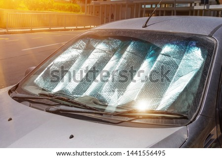 Protective reflective surface under the windshield of the passenger car parked on a hot day, heated by the sun's rays inside the car #1441556495
