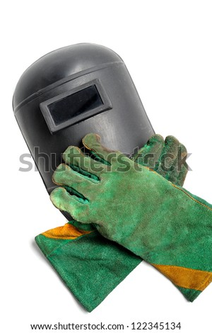 protective welding mask and green used welding gloves on white background