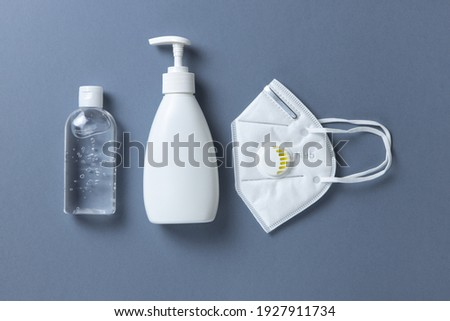 Protective, white face mask N 95, building respirator, sanitizer gel, soap on gray background, close-up, flatly. Hygiene concept, personal protectional gear, prevention of spread of infections. Stock foto ©