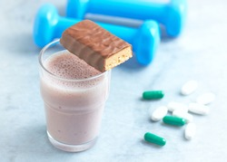 Protein bar, glass of protein shake with milk and raspberries. BCAA amino acids, L - Carnitine capsules and blue dumbbells in background. Sport nutrition. Bright background. Copy space.