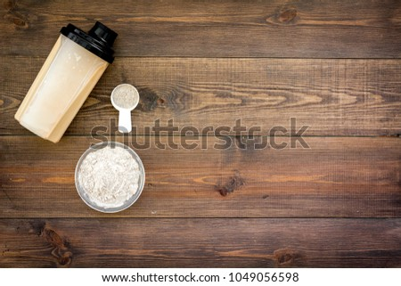 protein powder for fitness nutrition to start training on wooden background top view mock-up