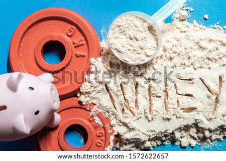 protein powder with the Word whey with piggy bank on blue background