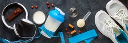 Protein shake in bottle, powder, bars and measuring tape on dark background. Top view. Sport food concept. Flat lay