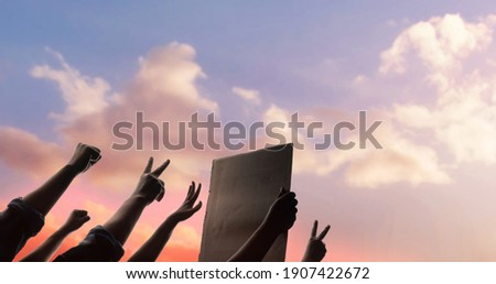 Protest, Mob, Expression and Strike Concept.  Silhouette of People Raise Up Hands into the Sky. the Leader Holding a Corrugated Paper. Foto stock ©