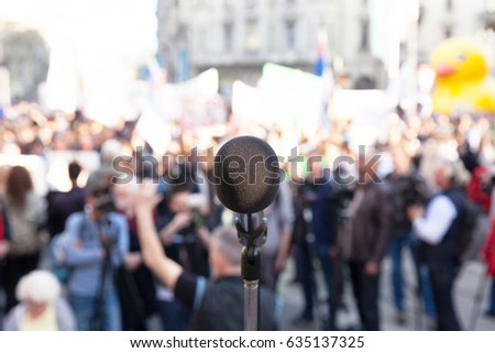 Protest. Political rally. Demonstration. Microphone in focus, blurred crowd in background.