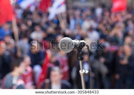 Protest. Public demonstration. Microphone in focus against blurred audience. Stock photo ©