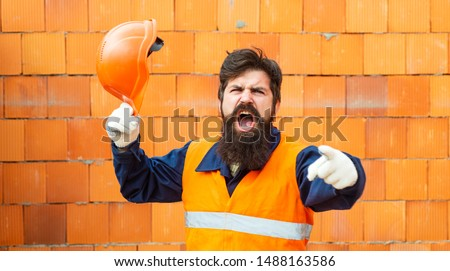 Protest. The builder screams. A man in a protective yellow vest. Salary. Strike. Low pay. Hard work. Handyman. Foreman at a construction site angry and aggressive