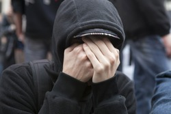 protestant anarchist close his face by hands for saving privacy