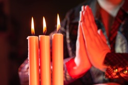 Protestant prayer against the background of burning candles. Hands folded in prayer. A woman prays to God. Burning candles and the hands of a Protestant woman. Christian religion.