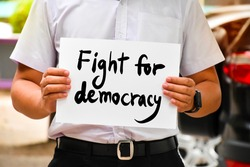 Protester holds wordcard 'Fight for democracy', concept for calling all people to be protesters and fight for democracy from revolutions, coups, and restrictions on freedom from the people.