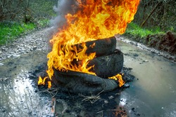Protesters burn car tires on a country road. Fire, black smoke, strong odor and release of toxic gases