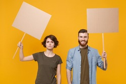 Protesting young two people guy girl hold in hands protest signs broadsheet blank placard on stick isolated on yellow background studio portrait. Protests strikes pickets concept. Youth against city