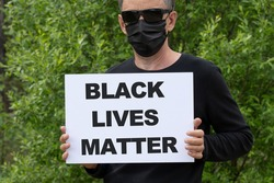 Protests broke out across the United States over the death of George Floyd. A man in a medical black mask and black glasses holds a white banner with the text BLACK LIVES MATTER.