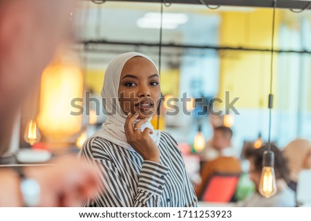 Protrait of a black ( african-american) female muslim standing in a modern business office while wearing a hijab.
