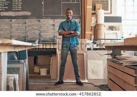 Proud African small business owner standing in his studio workshop