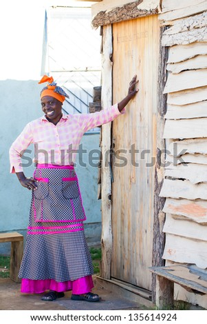 proud african woman leaning against her homes door smiling brightly