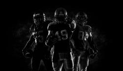Proud american football players in dark