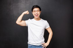 Proud and boastful handsome asian guy workout at gym, glex biceps to show girlfriend how strong he is, smiling pleased, do sports, exercise as having sportsman role-model, black background