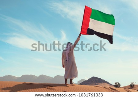 Proud arabian Emirati man holding a UAE flag in the desert
